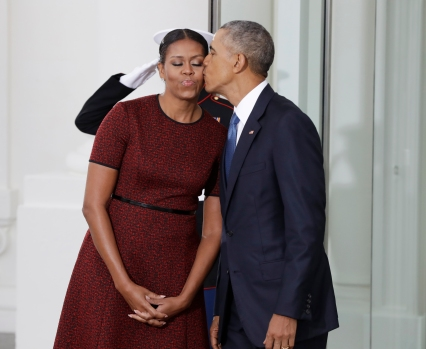 President Barack Obama kisses first lady Michelle Obama as they await for the arrival of President-elect Donald Trump and his wife Melania, Friday, Jan. 20, 2017, at the White House in Washington. (AP Photo/Evan Vucci)